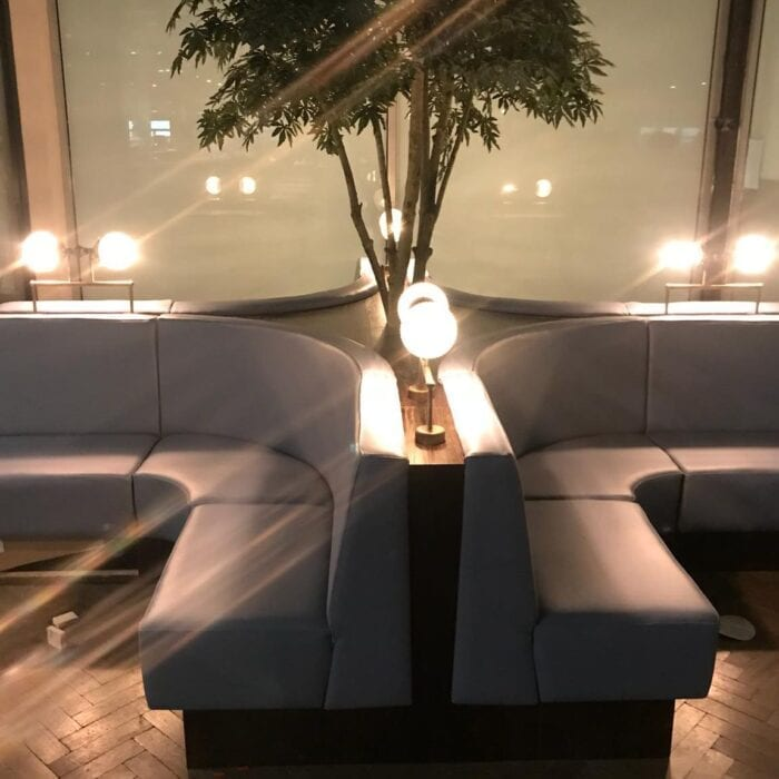 curved banquette seating with plant feature and lighting