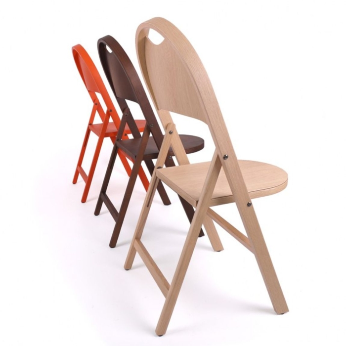 Diagonal row of Slim folding chairs folded out. Shows three different opyions of wood and lacquer finishes