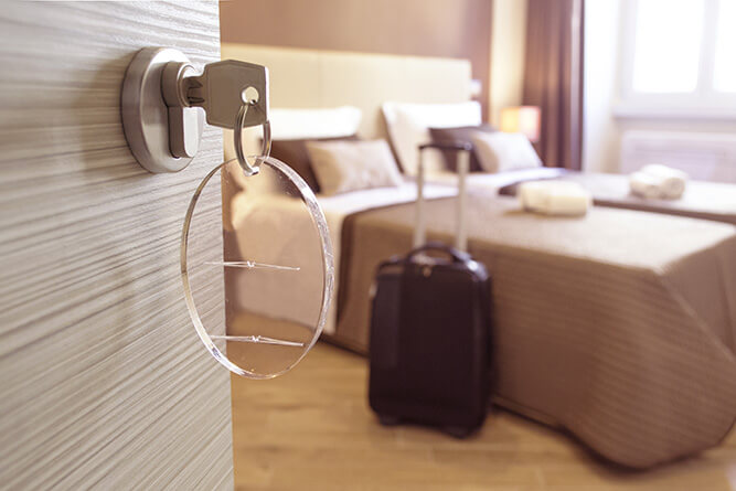 Hotel Room Door and key opening to hotel room with bed and travel bag
